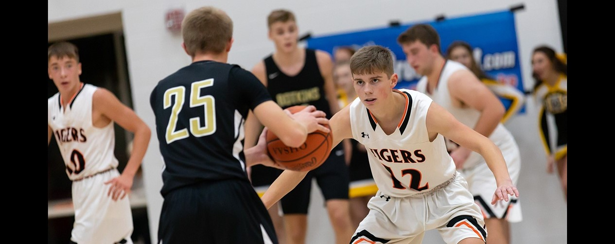 High school boys basketball player guarding his opponent