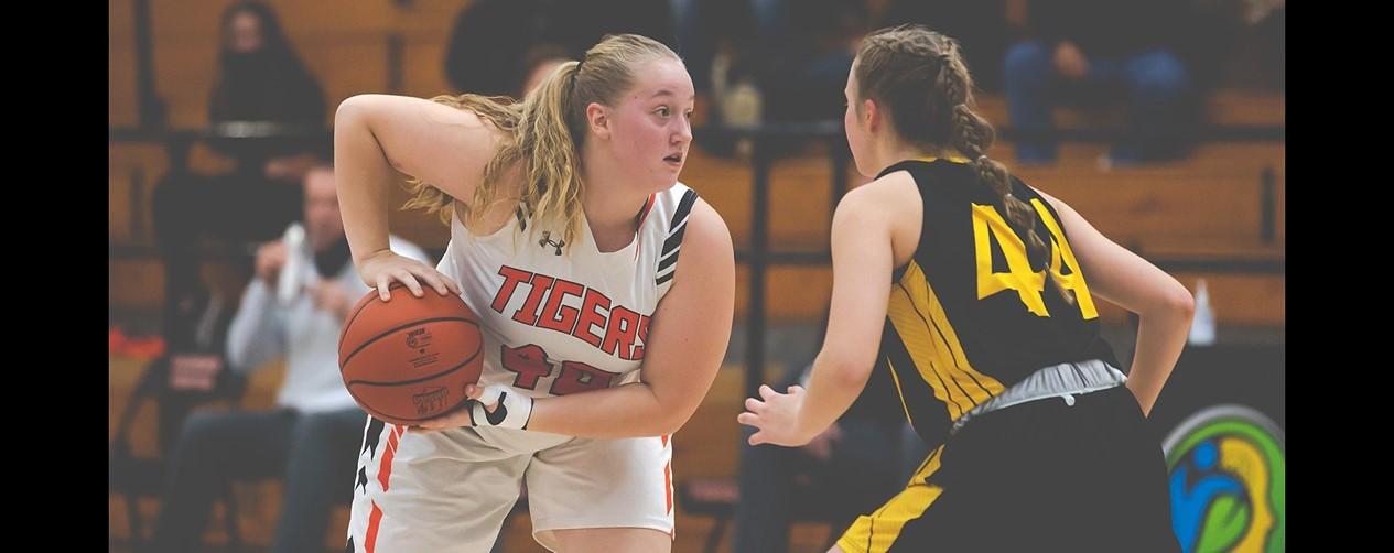High school girls basketball player keeping the ball away from opponent