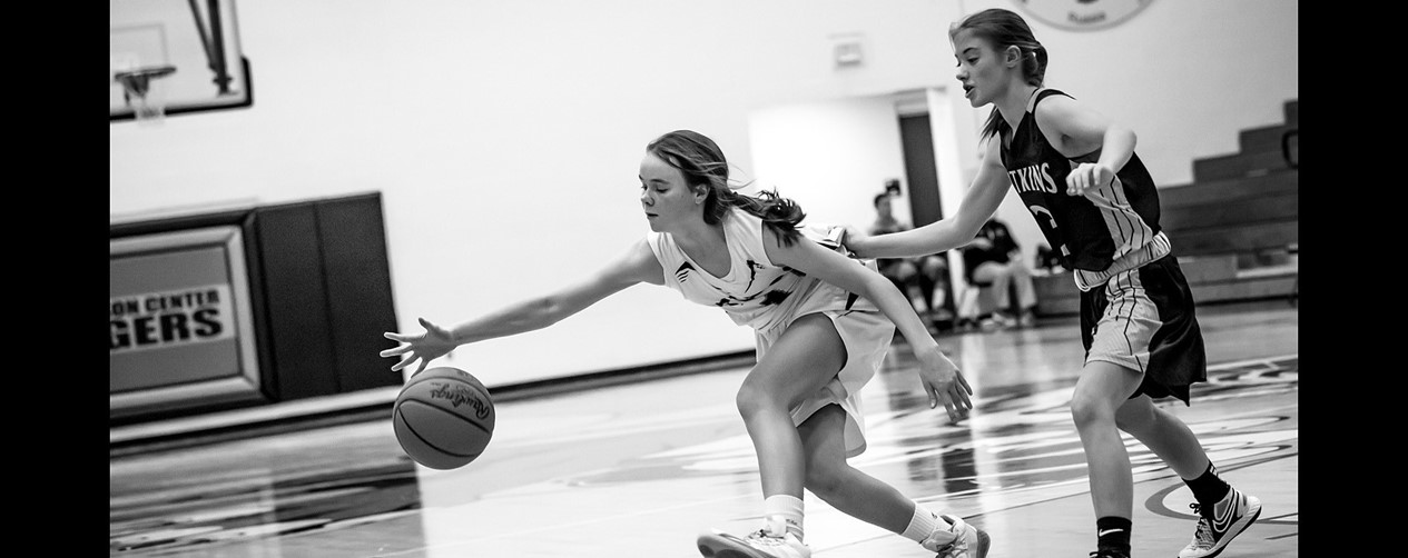 High school girls basketball player dribbling