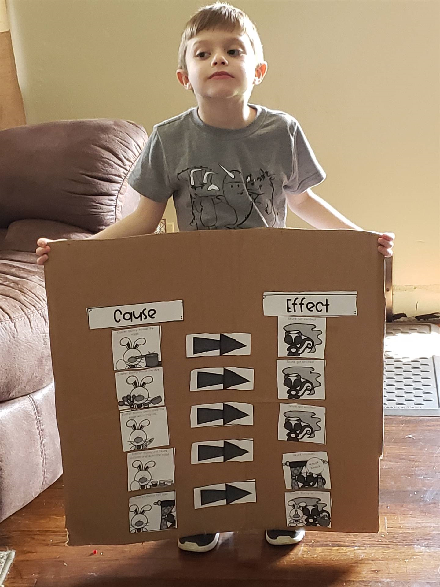 boy holding cardboard cause and effect poster