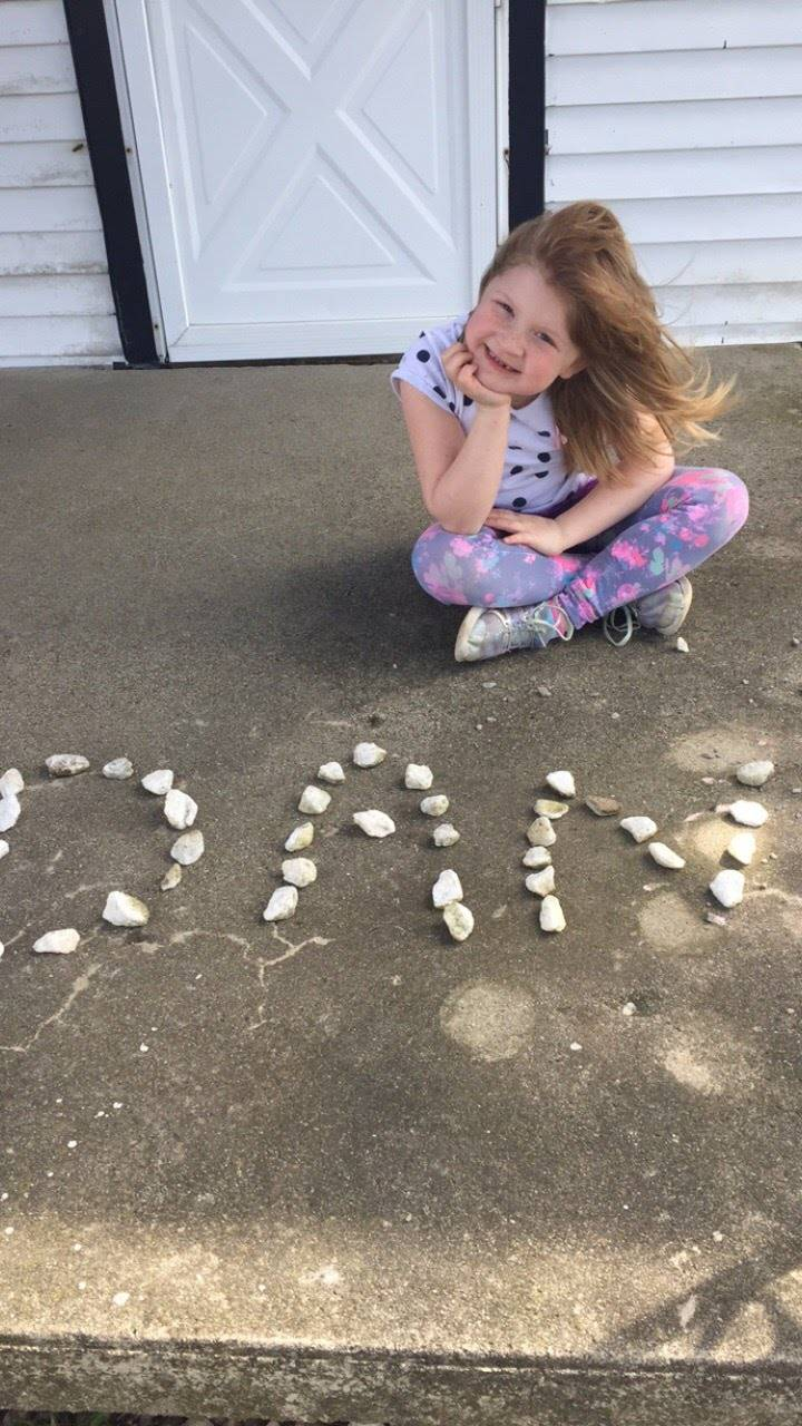 girl spelling name with shells