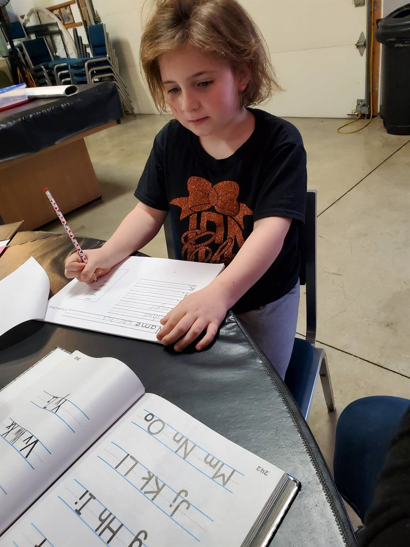 girl practicing letters of the alphabet with pencil and paper