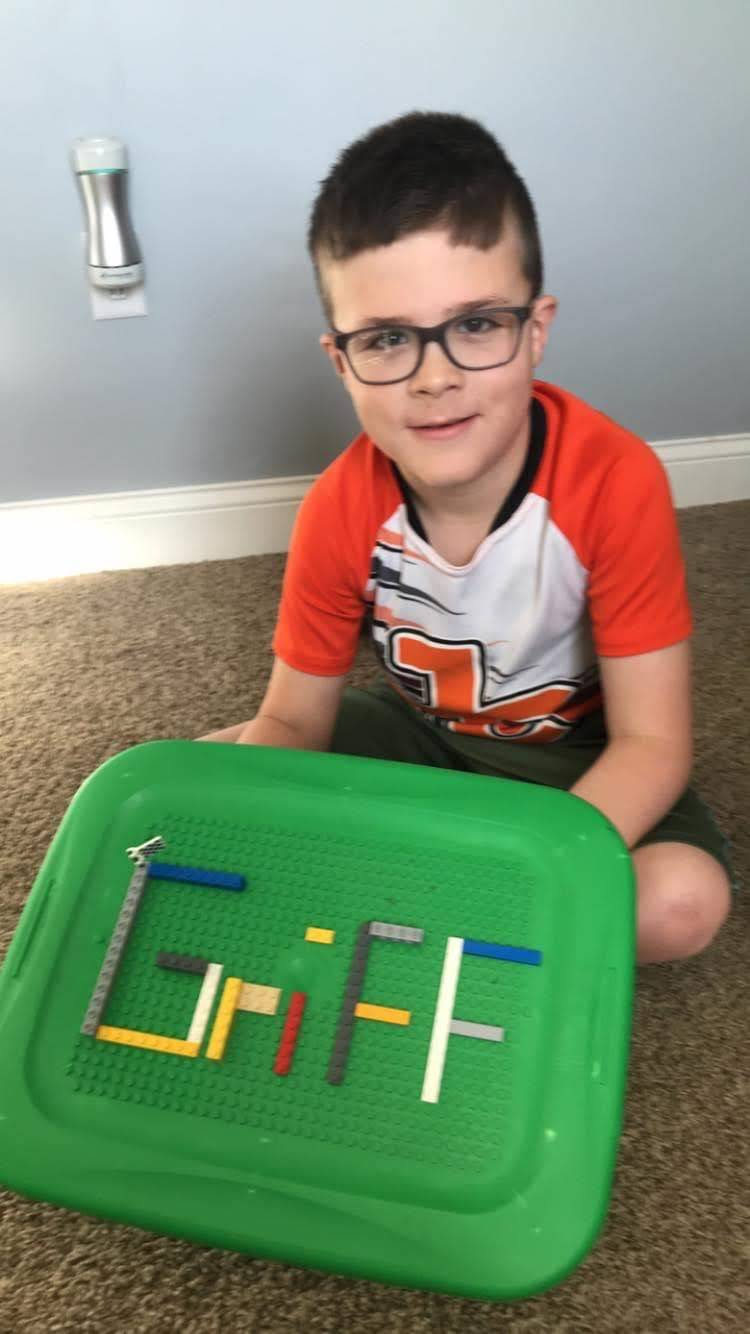 boy spelling his name with legos