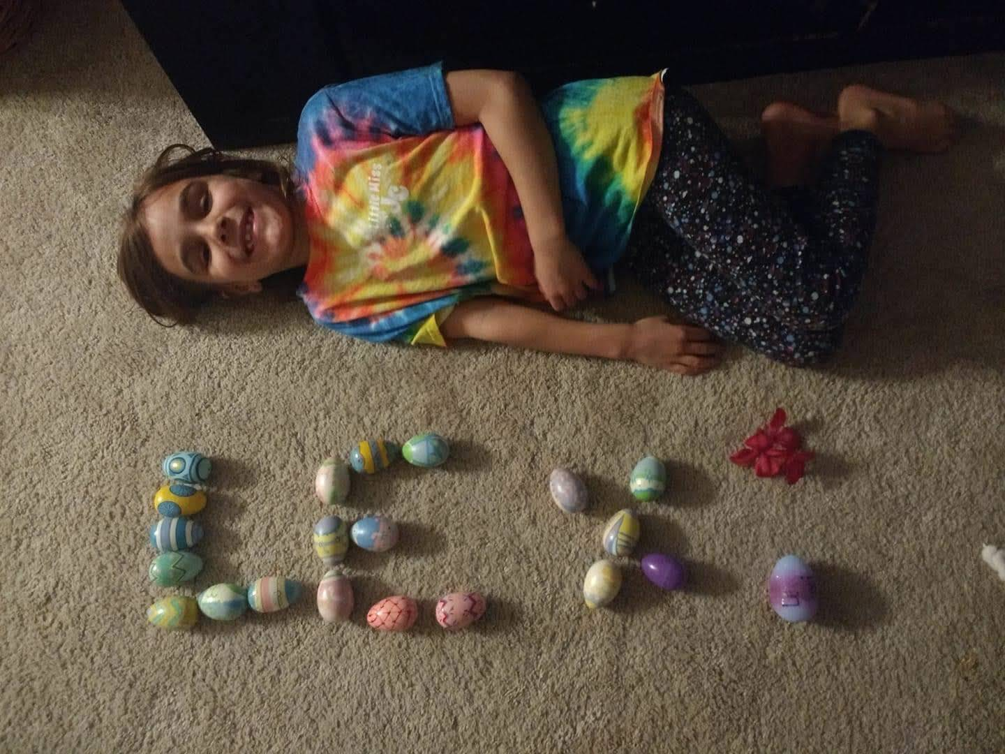 girl spelling her name with plastic easter eggs