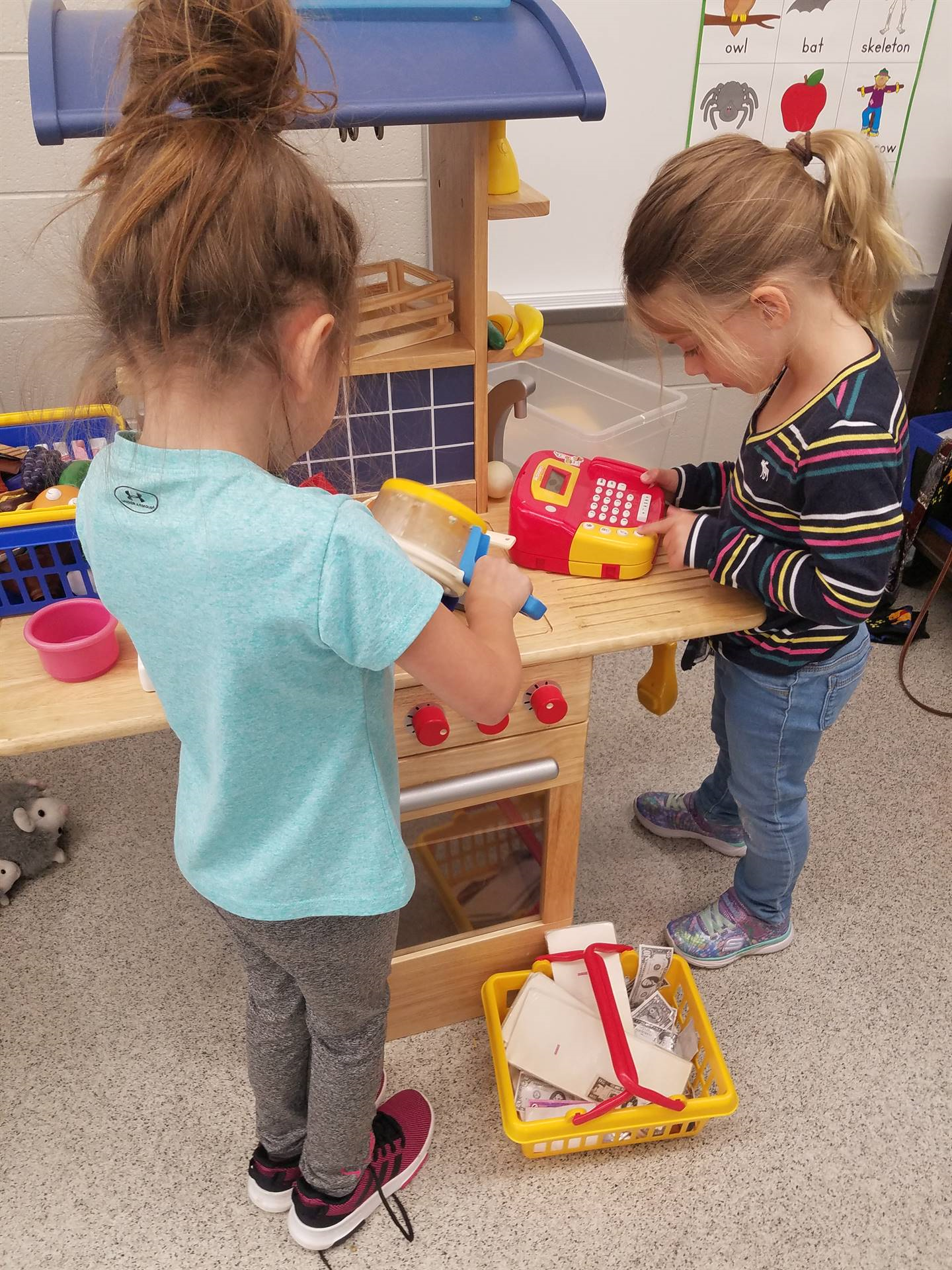 students in pretend kitchen in classroom