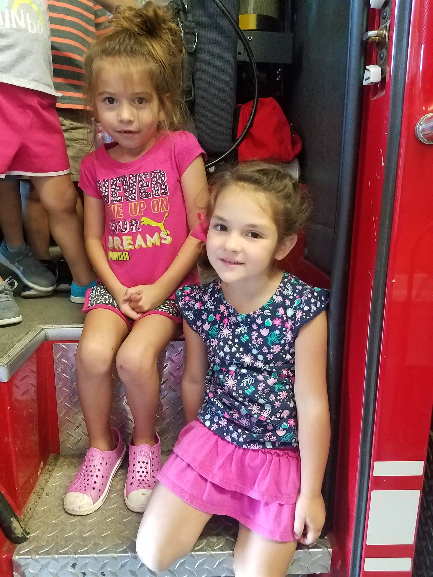 two girls on fire truck at the fire station