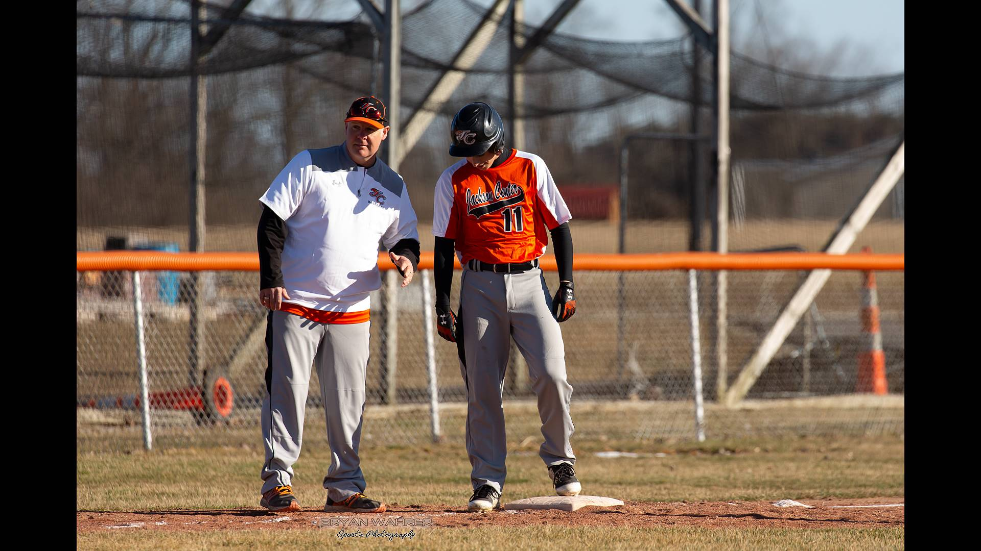 Coach talking to runner on base