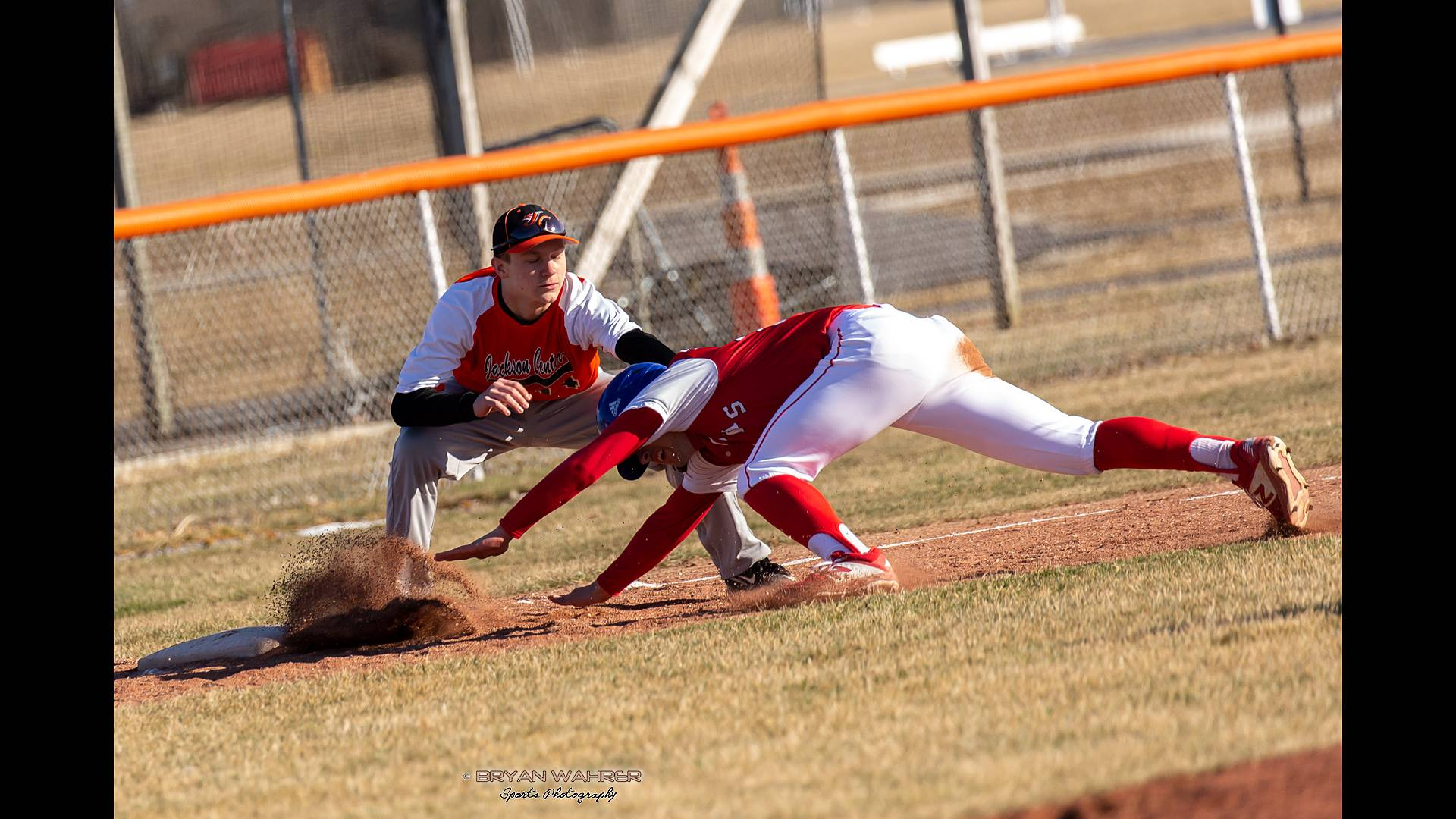 baseball player sliding into base and being tagged