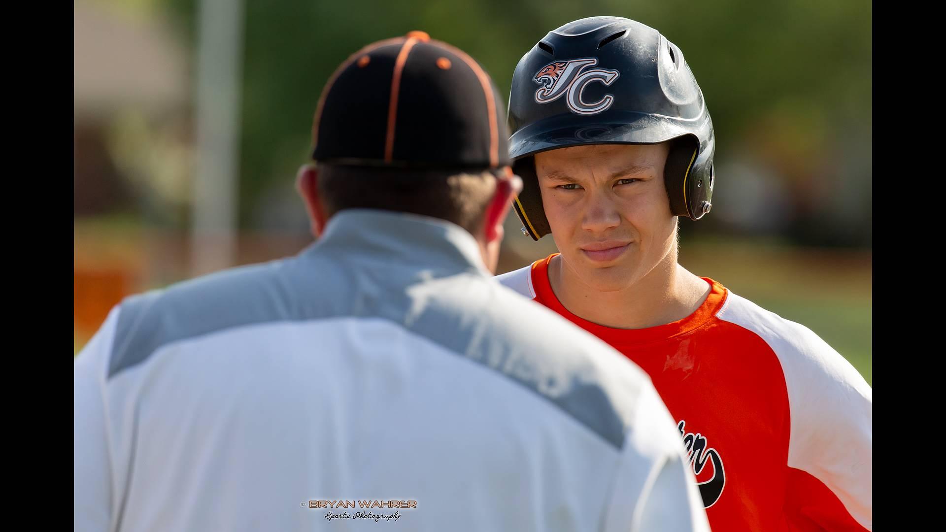 coach talking to baseball player