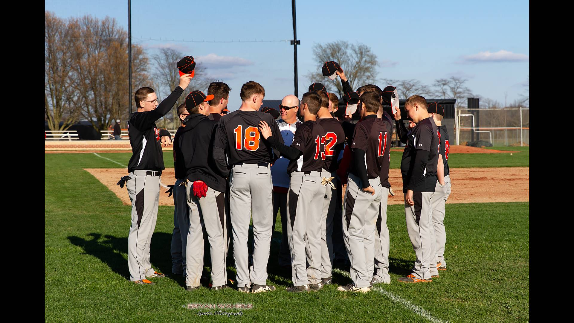 Baseball team group huddle with coach