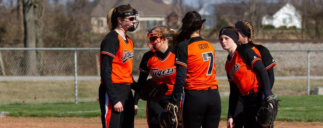 Softball girls meeting at the mound