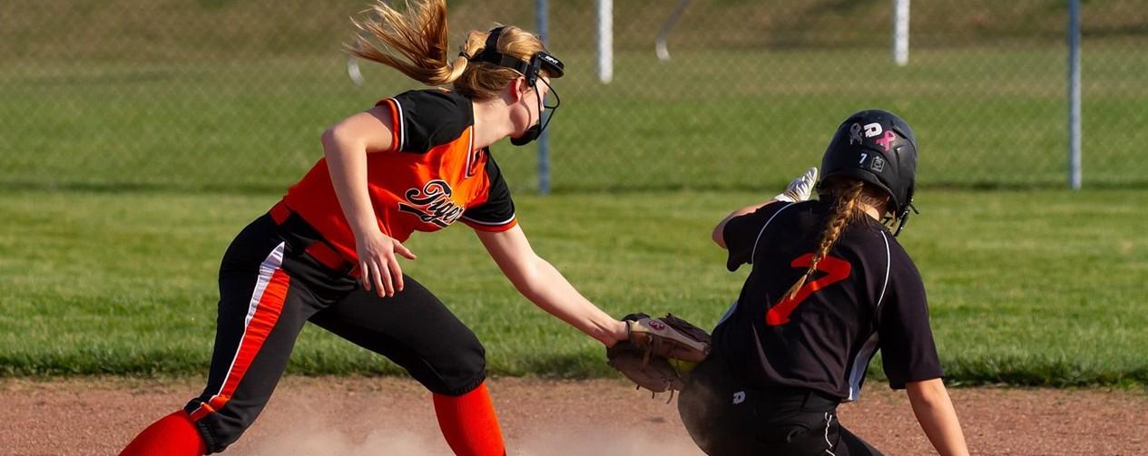 softball girl taggin the runner at base