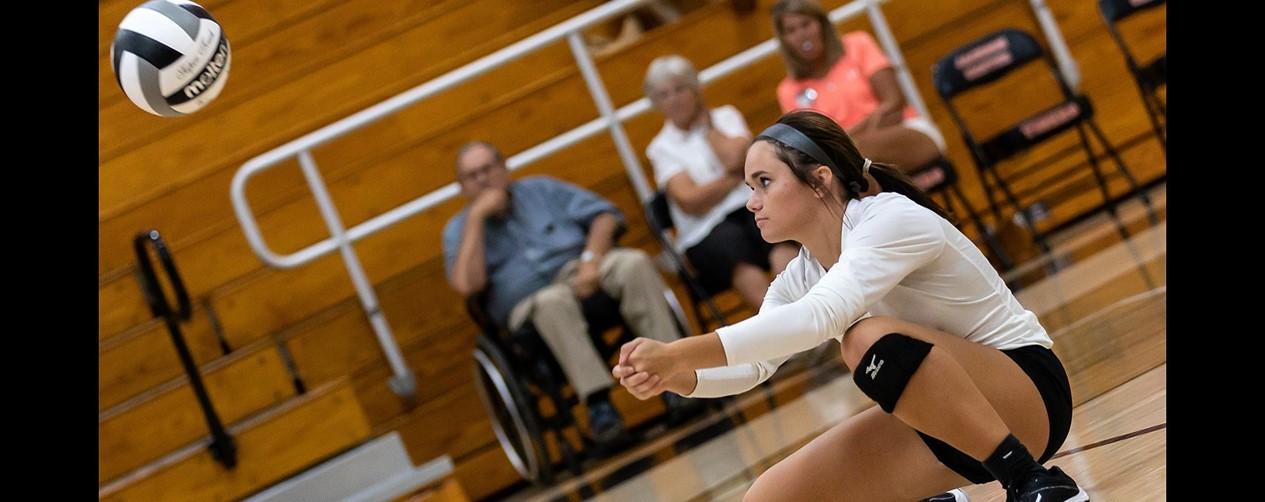 High school volleyball girl returning a serve